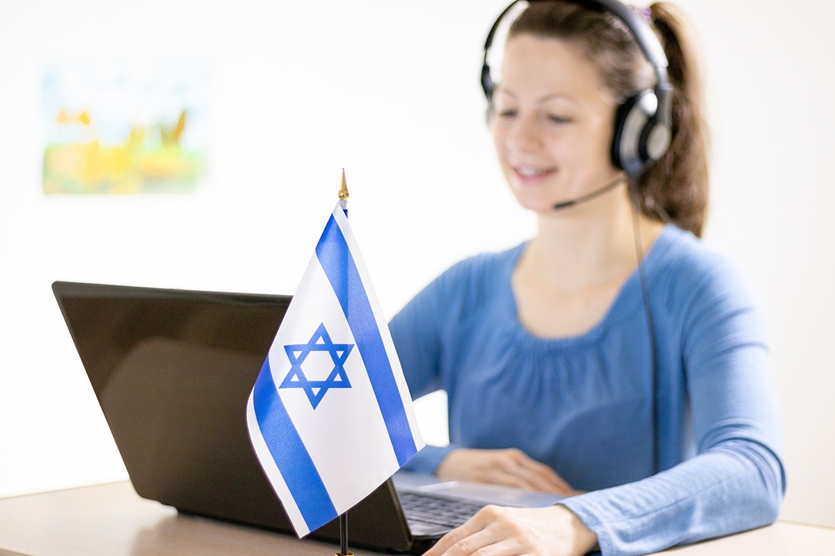 Young beautiful smiling woman sitting in front of a laptop with a Israeli flag on the table and communicating on a computer using a headset