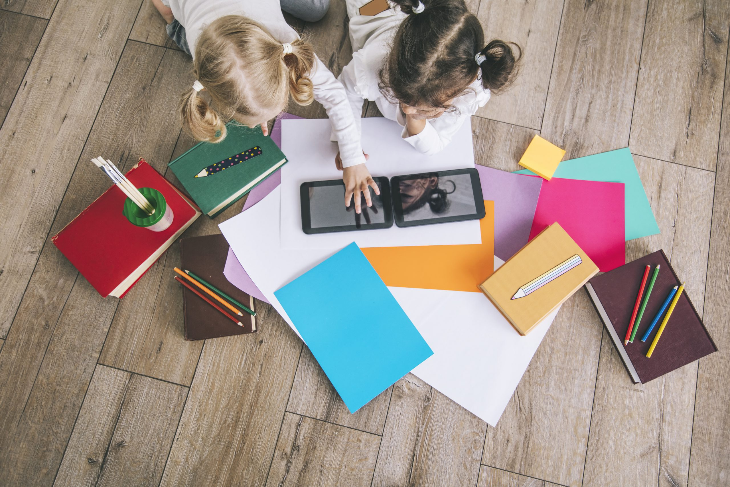 Two children, little girls of preschool age watching tablet at home on the floor